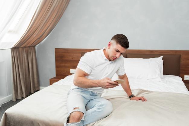 Homem, usando, smartphone, em, quarto hotel