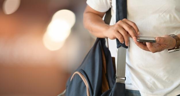 Homem, usando, smartphone, enquanto, carregar, mochila