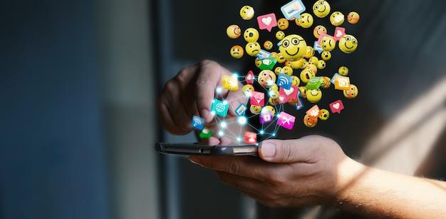 Homem usando smartphone, enviando ícones de emoticons de mensagens de texto. conceito de mídia social, renderização em 3d