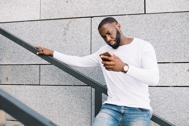 Homem, usando, smartphone, escada