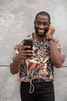 Homem usando smartphone moderno com fones de ouvido