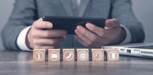 Homem usando smartphone. símbolos de contato em cubos de madeira