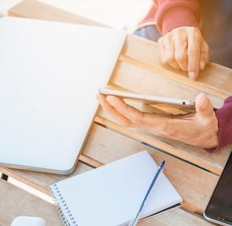 Homem usando tablet digital com laptop; bloco de notas em espiral e caneta na mesa de madeira