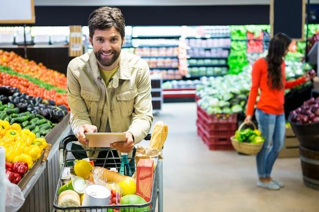 Homem usando tablet digital enquanto fazia compras no supermercado