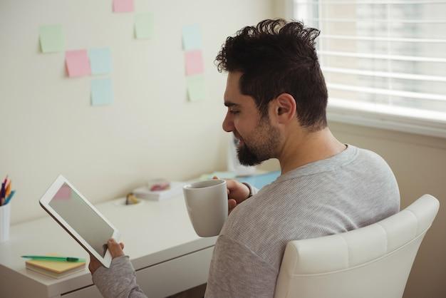 Homem usando tablet digital enquanto toma café
