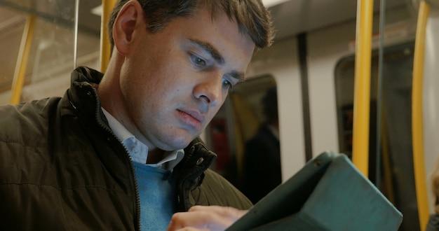 Homem usando tablet em trem do metrô