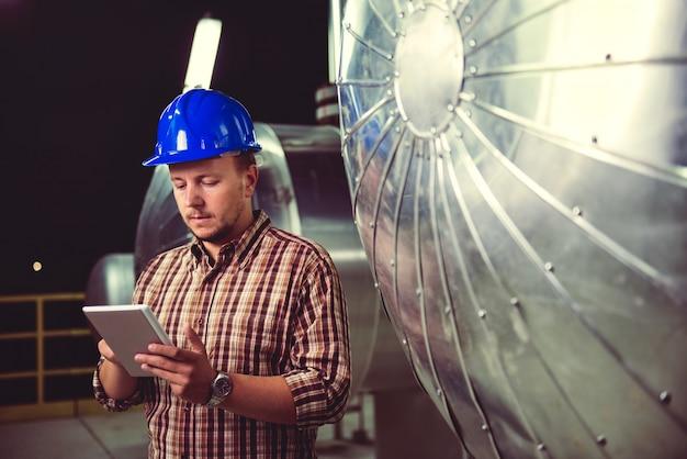 Homem usando tablet na instalação de processamento de gás natural