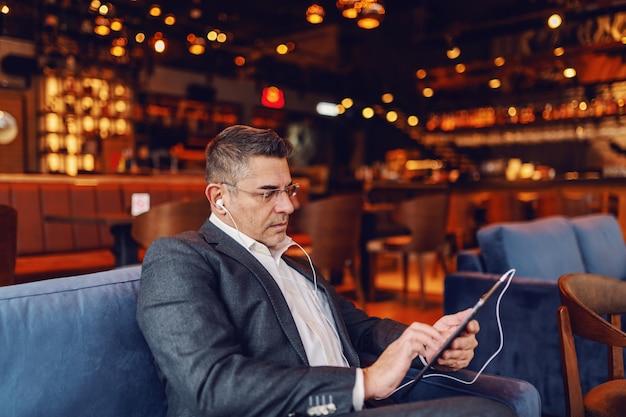 Homem usando tablet no café.