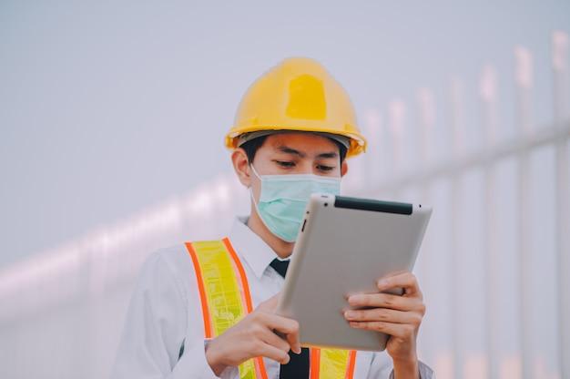 Homem usando tablet no canteiro de obras