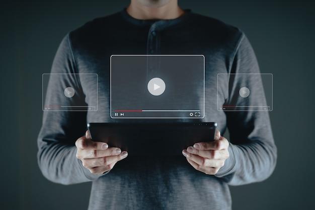 Homem usando tablet para assistir vídeo na internet, streaming online, aula online, criador de conteúdo