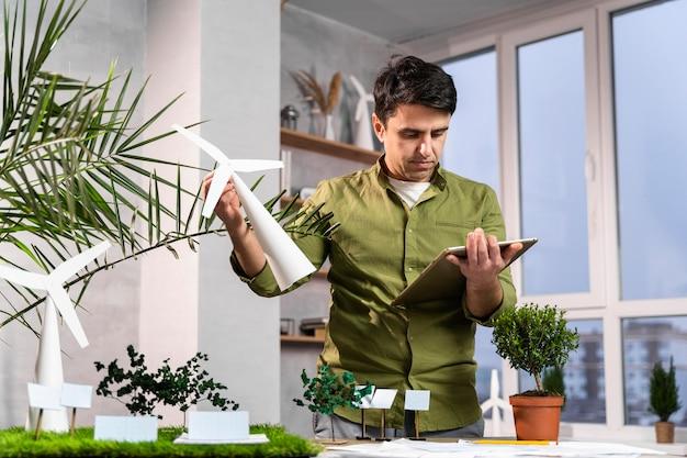 Homem usando tablet para um layout de projeto de energia eólica ecologicamente correto