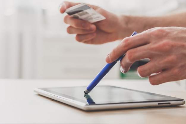 Homem usando tablet pc com caneta e cartão de crédito na mesa, fazendo compras online