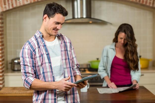 Homem, usando, tabuleta, em, cozinha, enquanto, mulher, jornal leitura, em, fundo