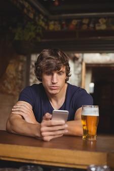 Homem usando telefone celular com copo de cerveja na mesa