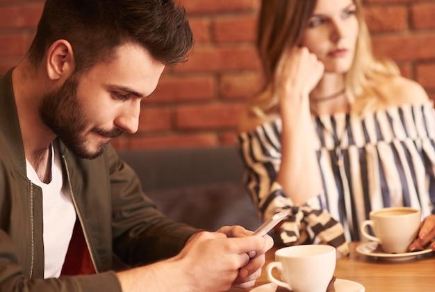 Homem usando telefone celular durante uma reunião com a namorada