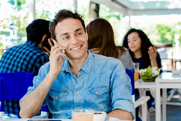 Homem usando telefone celular e bebendo café