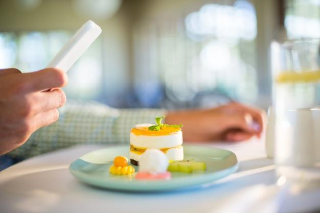Homem usando telefone celular enquanto almoça