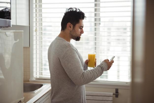 Homem usando telefone celular enquanto toma suco na cozinha