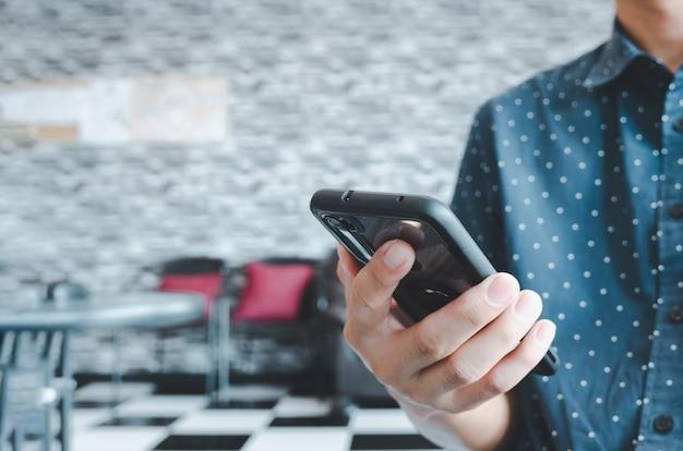 Homem usando telefone celular inteligente em uma cafeteria. copie o espaço