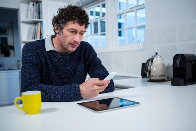 Homem usando telefone celular na cozinha