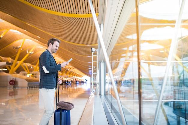 Homem usando telefone celular no aeroporto olhando através da janela