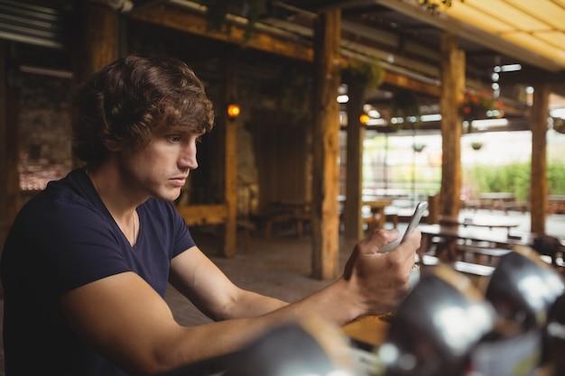 Homem usando telefone celular no balcão de bar