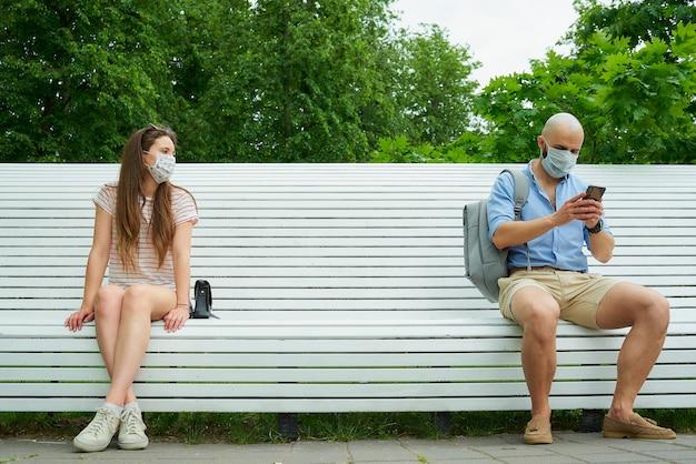 Homem usando telefone e jovem mulher sentada em extremos opostos de um banco, mantendo distância um do outro para evitar a propagação do coronavírus.