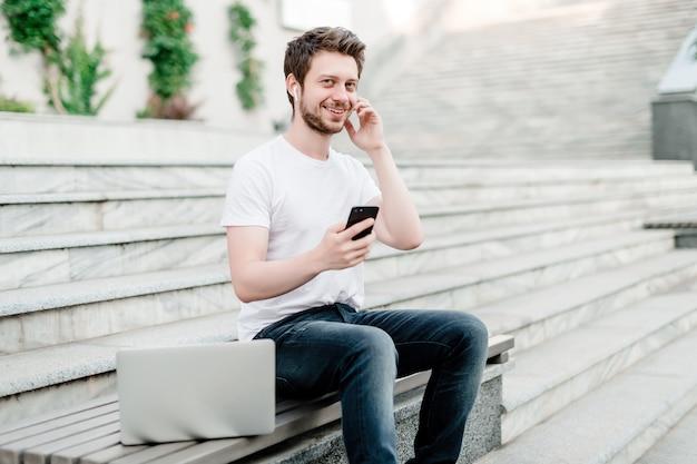 Homem, usando, telefone, e, laptop, ligado, a, banco