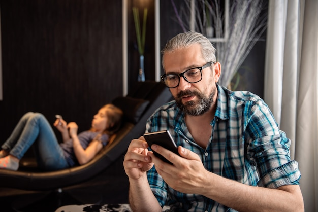 Homem usando telefone inteligente em casa