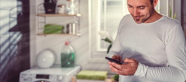 Homem usando telefone inteligente enquanto passando roupas