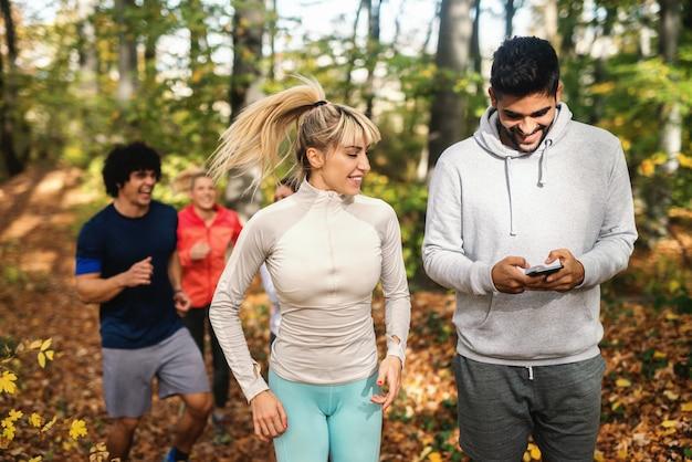 Homem usando telefone inteligente enquanto seus amigos correndo na floresta. estação do outono.