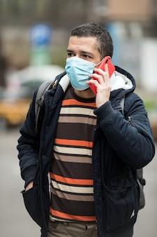 Homem usando telefone inteligente na cidade usando máscara facial por causa da poluição do ar