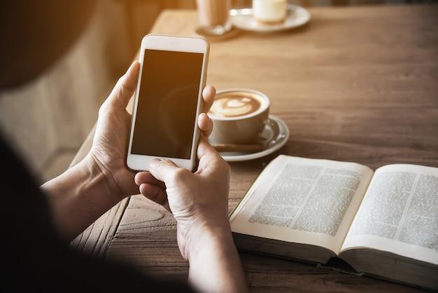 Homem, usando, telefone móvel, bebendo um café, e, lendo um livro
