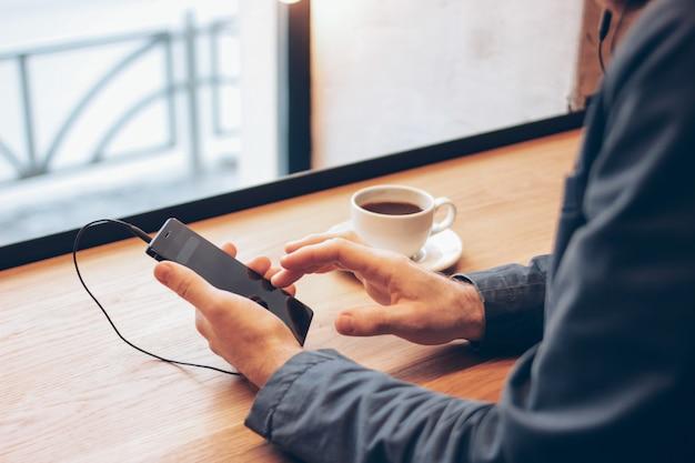 Homem, usando, telefone móvel, com, fones, em, café