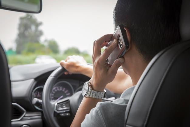 Homem, usando, telefone móvel, conversa um tempo, dirigindo um carro