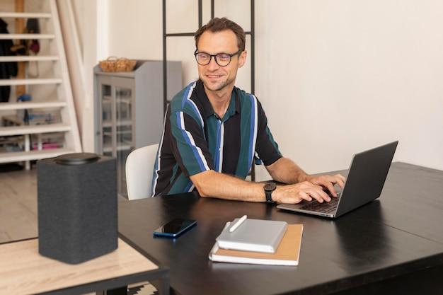 Homem usando um alto-falante inteligente enquanto trabalha