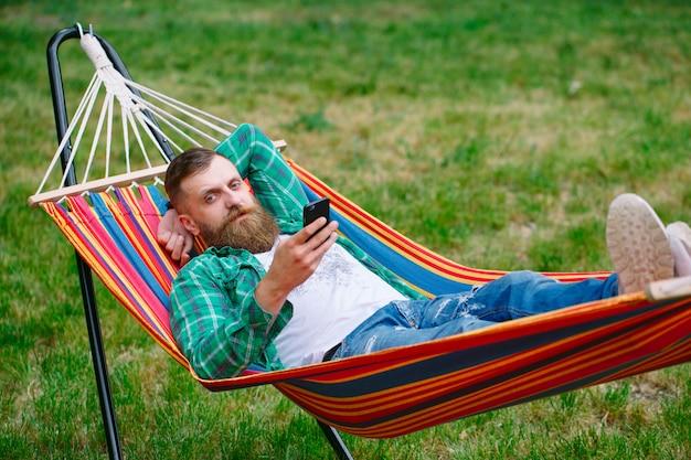 Homem usando um aplicativo em seu telefone móvel branco balançando numa rede