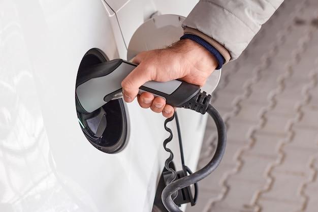 Homem usando um cabo de alimentação e plugue para carregar o carro elétrico na estação de carregamento de ev.
