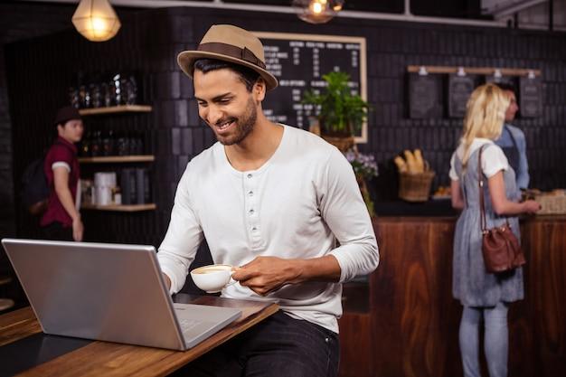 Homem usando um laptop e bebendo café