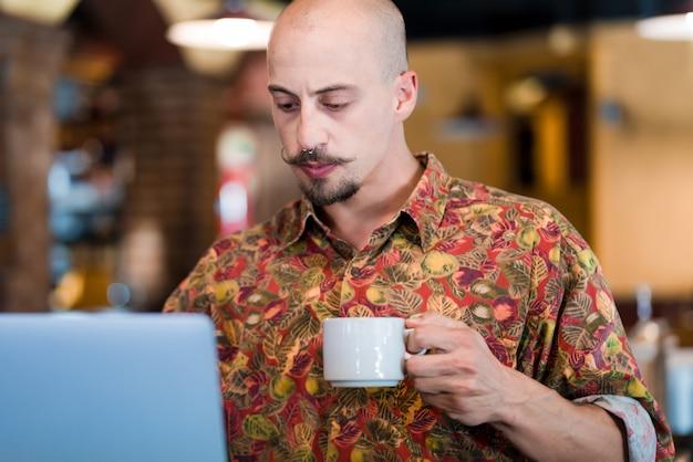 Homem usando um laptop e bebendo uma xícara de café enquanto está sentado em uma cafeteria dentro de casa.