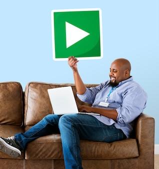 Homem usando um laptop e segurando um botão de play