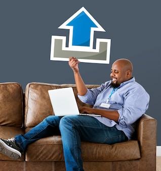 Homem usando um laptop e segurando um ícone de upload