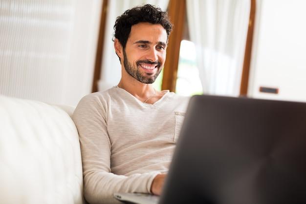 Homem usando um laptop enquanto está sentado no sofá