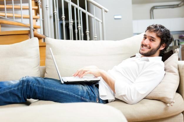 Homem usando um laptop enquanto relaxa no sofá