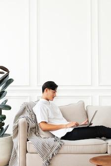 Homem usando um laptop no sofá em uma sala de estar com decoração escandinava