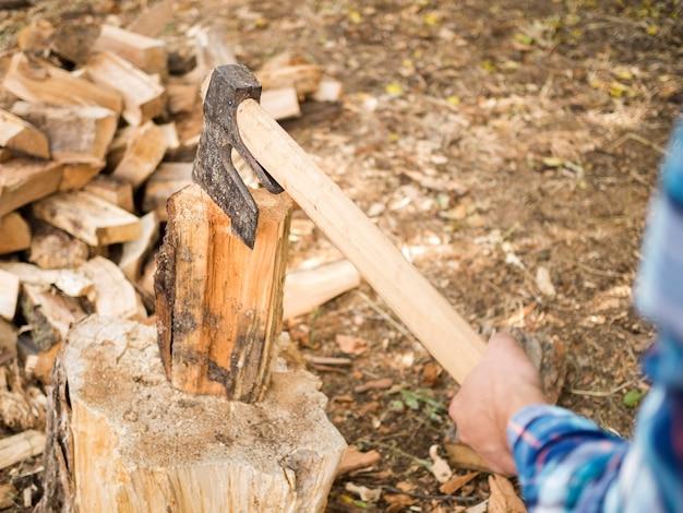Homem usando um machado para cortar madeira