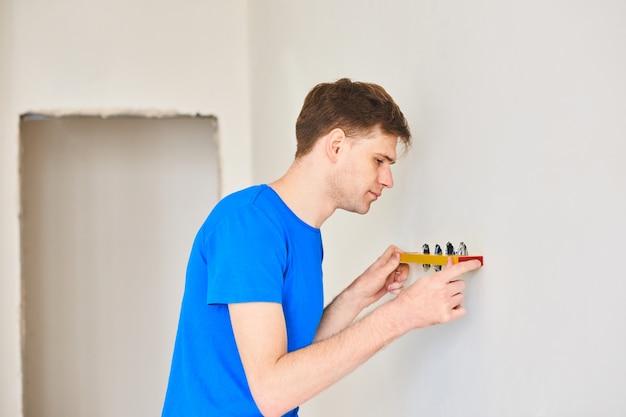 Homem usando um nível de bolha para sondar uma parede. conceito de renovação em casa.