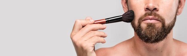 Homem usando um pincel de maquiagem no rosto com espaço de cópia