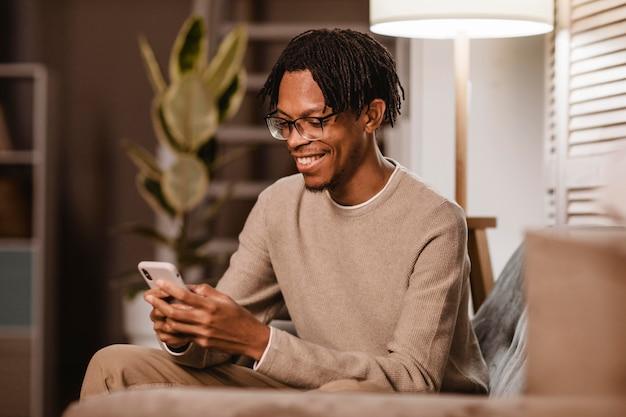 Homem usando um smartphone moderno enquanto está no sofá em casa