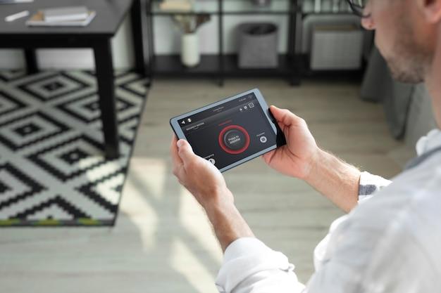 Homem usando um tablet doméstico inteligente dentro de casa
